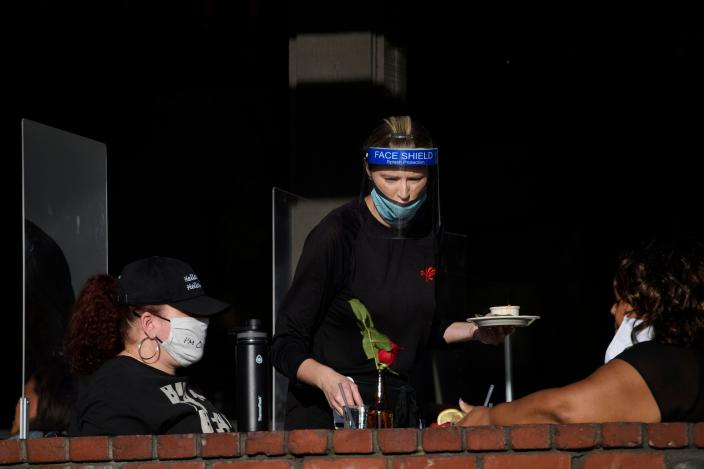 A waiter wearing personal protective equipment (PPE) serves customers dining outdoors in Manhattan Beach, California, November 21, 2020 a few hours before the start of the new 10:00 pm to 5:00 am curfew during increased Covid-19 restrictions. - The United States surpassed 12 million Covid-19 cases today, according to the Johns Hopkins University real-time tracker. (Photo by Patrick T. Fallon / AFP) (Photo by PATRICK T. FALLON/AFP via Getty Images)