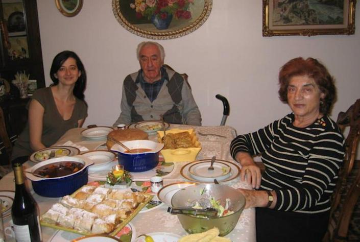 A younger woman sits at a table with two older people.