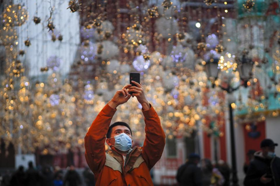 A tourist wearing a face mask to help curb the spread of the coronavirus takes a photo in Nikolskaya street near Red Square in Moscow, Russia, Friday, Nov. 13, 2020. Coronavirus infections in Russia kept on rising this week, with authorities reporting a record-high 21,983 new cases on Friday, bringing the country's total to nearly 1.9 million. A series of restrictions aimed at curbing the outbreak took effect Friday in Moscow. (AP Photo/Alexander Zemlianichenko)