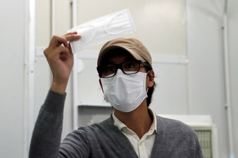 Mask Factory founder Mr. Tang, checks a prototype face mask at his factory, following the outbreak of the new coronavirus, in Hong Kong
