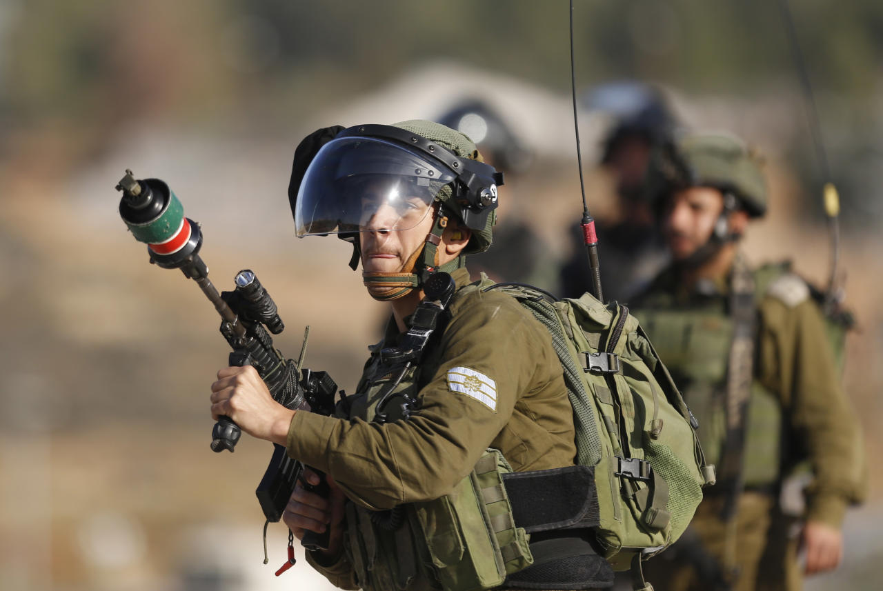 An Israeli soldier fires teargas toward Palestinians during clashes following a demonstration in support of Palestinian prisoners in Nabi Saleh near the West Bank city of Ramallah, Saturday, Jan. 13, 2018 . (AP Photo/Majdi Mohammed)