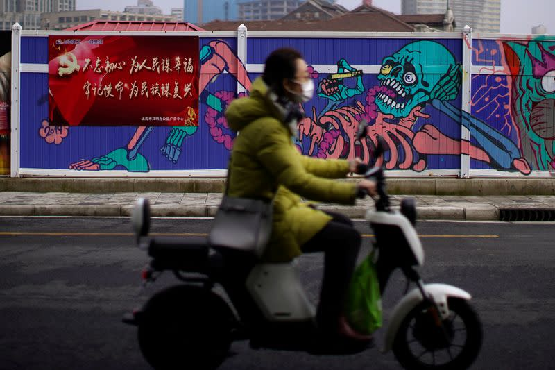 A woman wearing a mask is seen in front of a wall painted with graffiti at a construction site in Shanghai