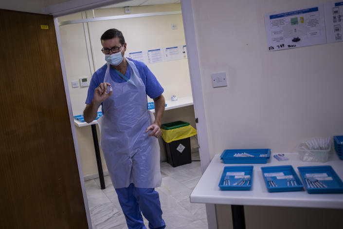"""A health worker holds a Pfizer-BioNTech COVID-19 vaccine at the vaccination centre in Gibraltar, Thursday, March 4, 2021. Gibraltar, a densely populated narrow peninsula at the mouth of the Mediterranean Sea, is emerging from a two-month lockdown with the help of a successful vaccination rollout. The British overseas territory is currently on track to complete by the end of March the vaccination of both its residents over age 16 and its vast imported workforce. But the recent easing of restrictions, in what authorities have christened """"Operation Freedom,"""" leaves Gibraltar with the challenge of reopening to a globalized world with unequal access to coronavirus jabs. (AP Photo/Bernat Armangue)"""
