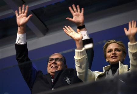 Prince Albert II of Monaco (L) and his wife Charlene wave from the presidential tribune at the opening ceremony of the 2014 Winter Olympics in Sochi, February 7, 2014. REUTERS/Lionel Bonaventure/Pool