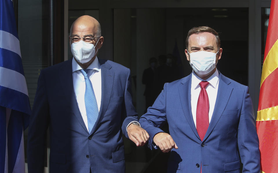 Greek Foreign Minister Nikos Dendias, left, and his North Macedonia's counterpart Bujar Osmani, right, pose for the cameras upon the arrival at the foreign ministry in Skopje, North Macedonia, Tuesday, Aug. 31, 2021. Greek Foreign Minister Dendias is on a one-day official visit to North Macedonia. (AP Photo/Boris Grdanoski)