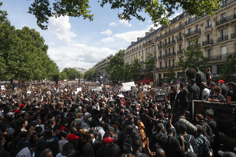 People listen to Assa Traore, right, during a demonstration against police brutality and racism in Paris, France, Saturday, June 13, 2020, organized by supporters of her brother Adama Traore, who died in police custody in 2016 in circumstances that remain unclear despite four years of back-and-forth autopsies. The demonstration is expected to be the biggest of several demonstrations Saturday inspired by the Black Lives Matter movement in the U.S., and French police ordered the closure of freshly reopened restaurants and shops along the route fearing possible violence. (AP Photo/Thibault Camus)
