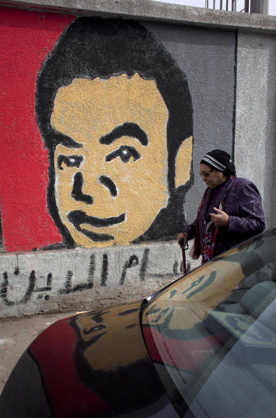 "An Egyptian woman passes by a mural depicting a slain Ultras member supporting the Cairo-based Al-Ahly club, who was killed in a soccer riots last year, part of murals that cover the sidewall of their soccer club facility in Cairo, Egypt, Thursday, Feb. 14, 2013. Arabic at the mural reads the name of the slain soccer fan ""Hussam Eddin."" (AP Photo/Nasser Nasser)"