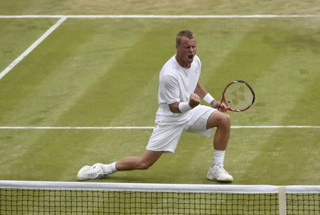 Lleyton Hewitt of Australia celebrates winning the fourth set during his men's singles match against Jerzy Janowicz of Poland at the Wimbledon Tennis Championships, in London
