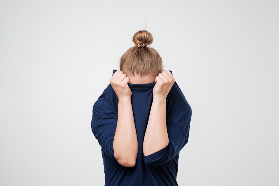 European woman hiding face under the clothes. She is pulling sweater on her head. Depressed emotion. Wish to be alone.