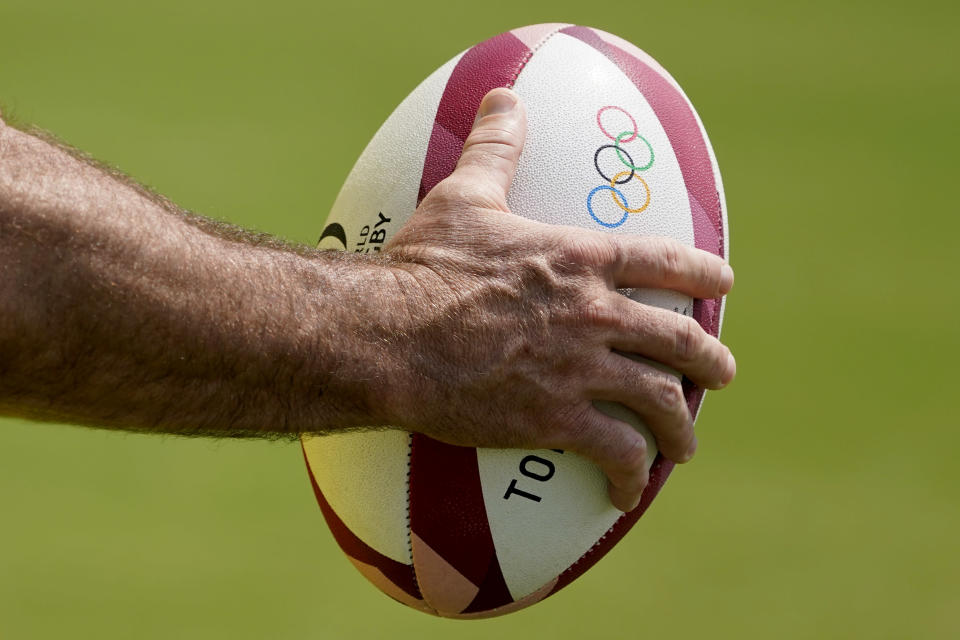 A member of Australia's men's rugby sevens team holds a ball during a practice at the Tokyo 2020 Olympics, in Tokyo, Friday, July 23, 2021. (AP Photo/David Goldman)