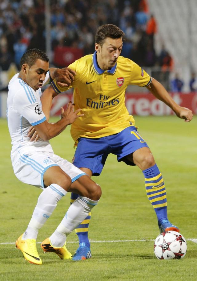 Arsenal's Mesut Ozil challenges Olympique Marseille's Dimitri Payet during their Group F Champions League soccer match at the Velodrome stadium in Marseille, September 18, 2013. REUTERS/Philippe Laurenson (FRANCE - Tags: SPORT SOCCER)