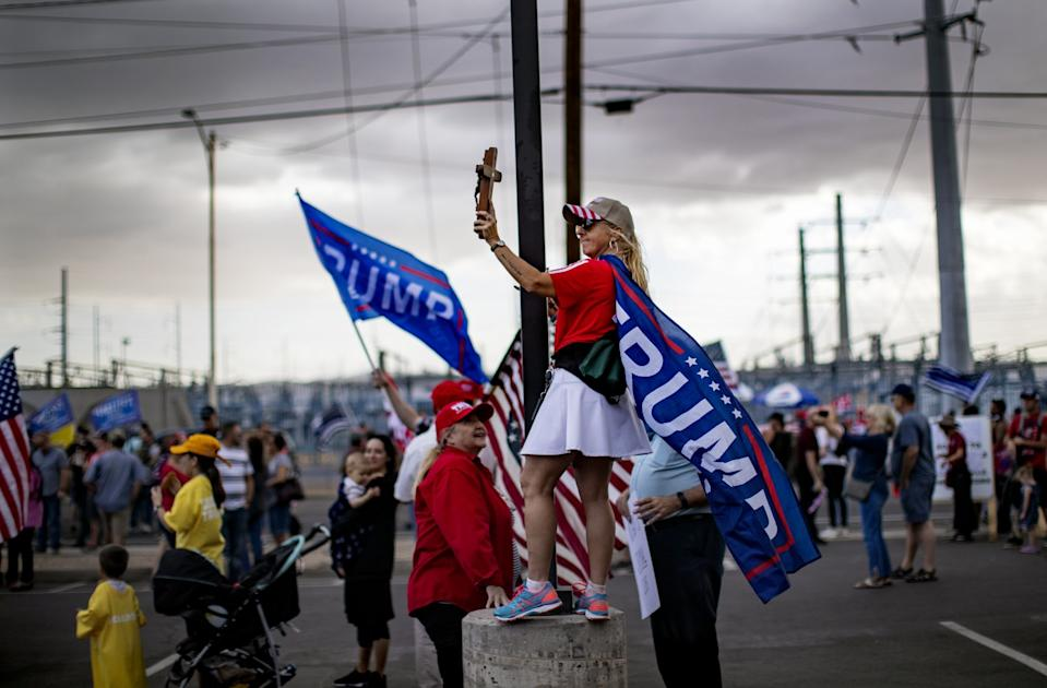 As storm clouds move in, a woman covered in Trump flags holds up a cross at a rally in Phoenix.