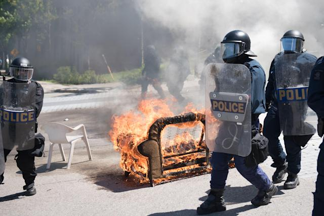 <p>Police walk past furniture set on fire by protesters during a demonstration in Quebec City on June 8, 2018, as the G7 Summits gets underway. (Photo: Alice Chiche/AFP/Getty Images) </p>