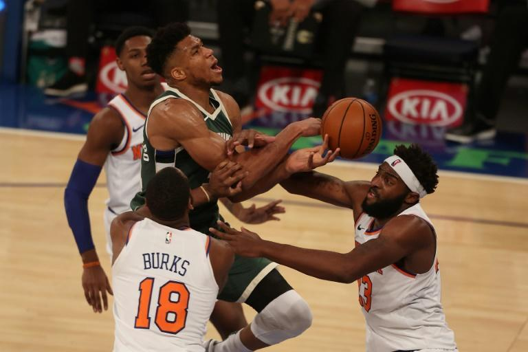 New York's Mitchell Robinson and Alec Burks defend against Milwaukee star Giannis Antetokounmpo in the Knicks' 130-110 NBA victory over the Bucks