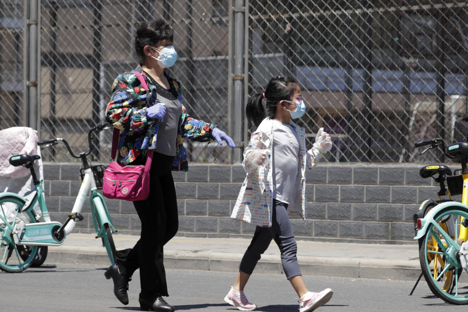 A woman and a child wearing protective face masks and gloves to help curb the spread of the new coronavirus arrive to a stadium to get a nucleic acid test in Beijing, Sunday, June 14, 2020. China is reporting its highest daily total of coronavirus cases in two months after the capital's biggest wholesale food market was shut down following a resurgence in local infections. (AP Photo/Andy Wong)