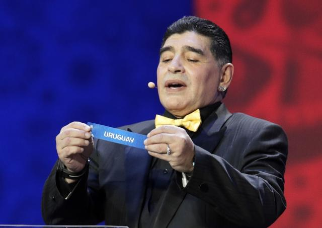Argentine soccer legend Diego Maradona holds up the team name of Uruguay during the 2018 soccer World Cup draw in the Kremlin in Moscow, Friday, Dec. 1, 2017. (AP Photo/Dmitri Lovetsky)