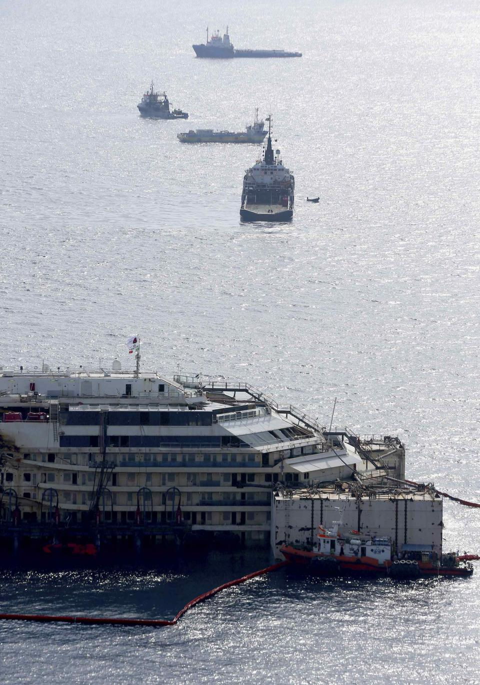Cruise liner Costa Concordia is seen surrounded by tugboats during a refloat operation at Giglio harbour at Giglio Island July 14, 2014. Technicians on Monday began a complex operation to refloat and tow away the wreck of the Costa Concordia, two and a half years after the luxury liner capsized off the Italian coast, killing 32 people. REUTERS/Alessandro Bianchi (ITALY - Tags: DISASTER TRANSPORT MARITIME)