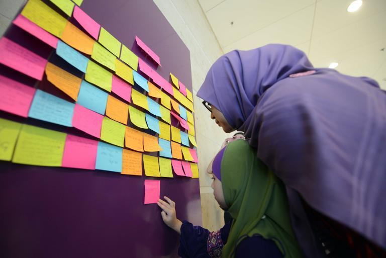 Rohaida Rudzlan (R) and six-year-old Airis Marisah (C) look at messages of support posted on a board for the relatives and passengers of missing AirAsia flight QZ8501, at in Singapore's Changi airport