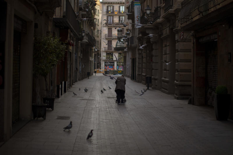 In this Saturday, March 21, 2020 photo, a woman pushes a cart with her belongings as she walks along an empty street in downtown Barcelona, Spain. While Spanish authorities tell the public that staying home is the best way to beat the coronavirus pandemic, some people are staying out because home has come to mean the streets of Madrid and Barcelona. (AP Photo/Emilio Morenatti)