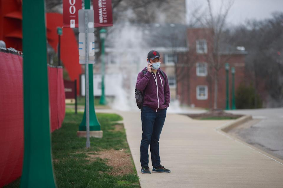 An international student at Indiana University waits for a bus near the university on March 20, when classes first went online because of the pandemic.