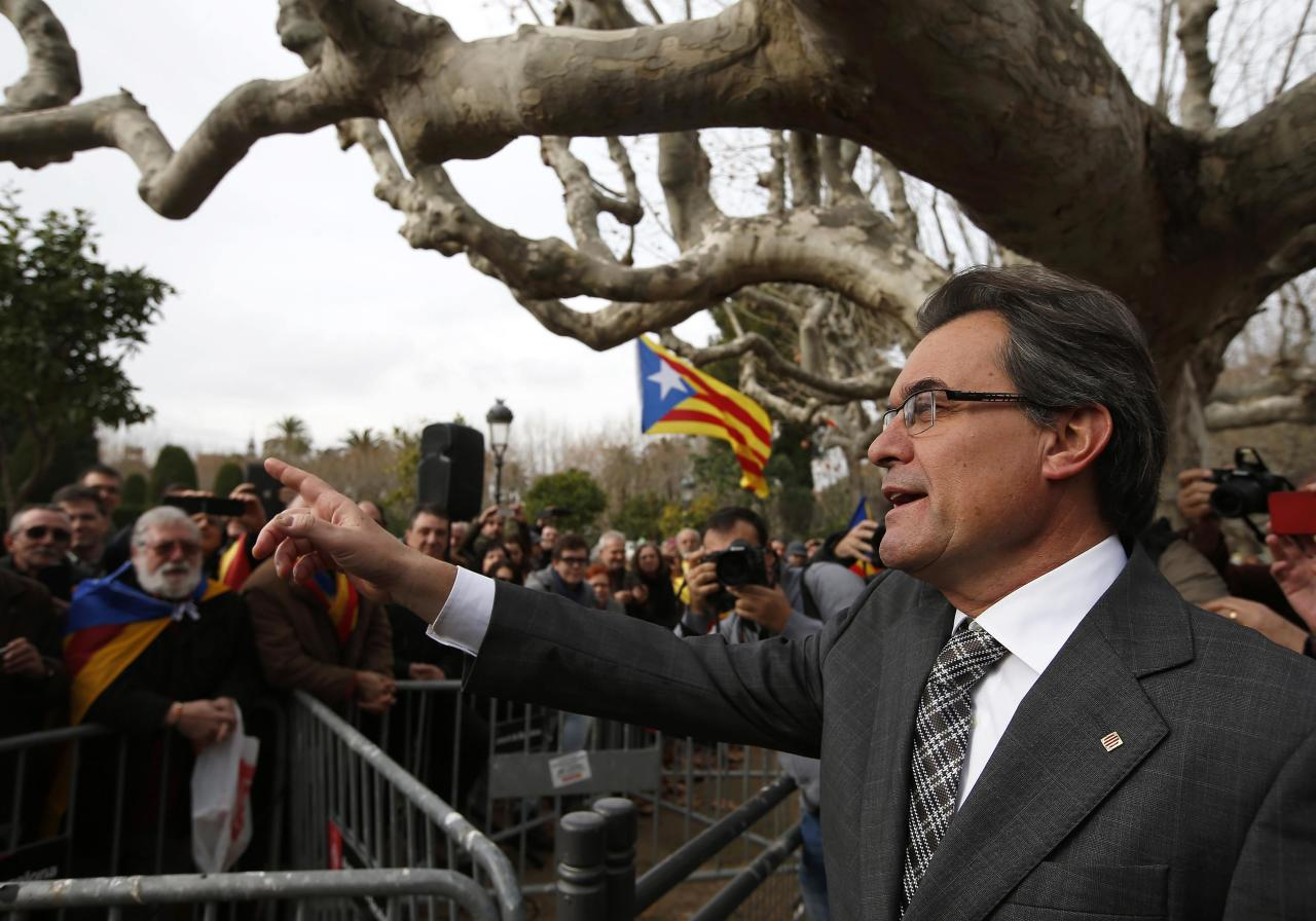 Catalonia's President Artur Mas waves to supporters after voting in the regional parliament in Madrid