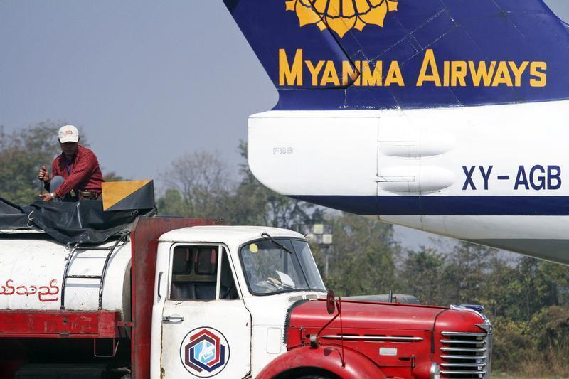 A man prepares to fuel an ageing Myanma Airways airplane in the city of Myitkyina