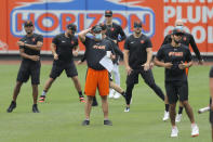 Baltimore Orioles manager Brandon Hyde, center in orange shorts, looks on as his team warms up during baseball training camp, Tuesday, July 7, 2020, in Baltimore. (AP Photo/Julio Cortez)