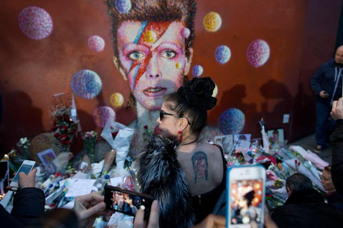 <p>JAN. 11, 2016 – A woman with a tattoo on her back looks at a mural of British singer David Bowie by artist Jimmy C in Brixton, south London. Bowie, the other-worldly musician who broke pop and rock boundaries with his creative musicianship, nonconformity, striking visuals and a genre-spanning persona he christened Ziggy Stardust, died of cancer Sunday aged 69. He was born in Brixton. (Matt Dunham/AP) </p>