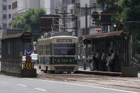 A commuter tram approaches to a stop in Hiroshima, western Japan, Monday, Aug. 3, 2020. A tram which survived the Hiroshima atomic bombing will run, without any passenger, on the streets on Aug. 6 to commemorate the day of atomic bombing in the city. (AP Photo/Eugene Hoshiko)