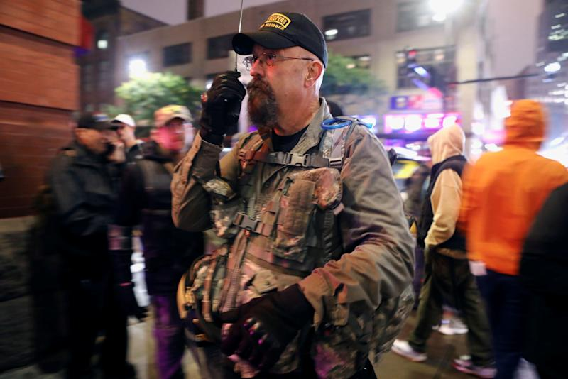 Members of the Oath Keepers militia group act as security to those leaving a rally by President Trump in Minneapolis, Minn.