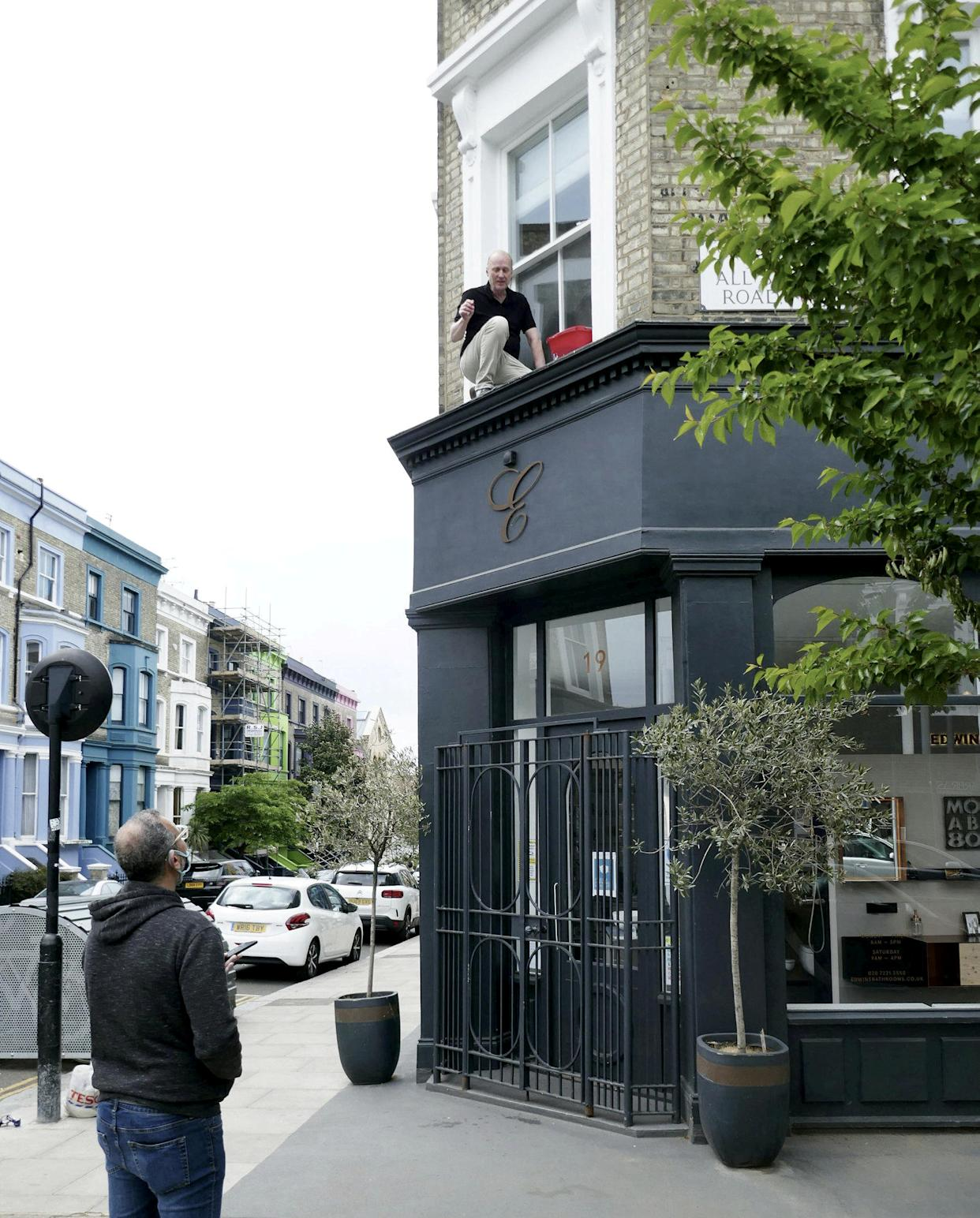 The hapless celebrity was photographed stuck on a ledge pleading for help from passer-bys. (Duncan Cumming/SWNS)