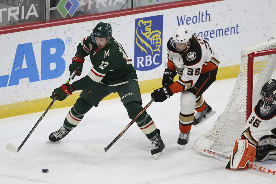 Minnesota Wild's Nick Bonino (13) controls the puck against Anaheim Ducks' Derek Grant (38) during the first period of an NHL hockey game Friday, May 7, 2021, in St. Paul, Minn. (AP Photo/Stacy Bengs)