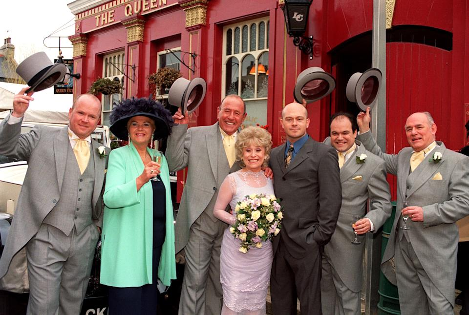 EastEnders stars Barbara Windsor (who plays bride 'Peggy Mitchell') and Mike Reid (groom 'Frank Butcher', third from left), with co-stars during a photocall outside the Queen Vic pub at London's Elstree studios, where their on-screen wedding reception was filmed.   * With fellow actors (l-r) Steve McFadden (Phil), Pam St Clement (Pat), Ross Kemp (Grant), Shaun Williamson (Barry) and Tony Caunter (Roy).   (Photo by John Stillwell - PA Images/PA Images via Getty Images)
