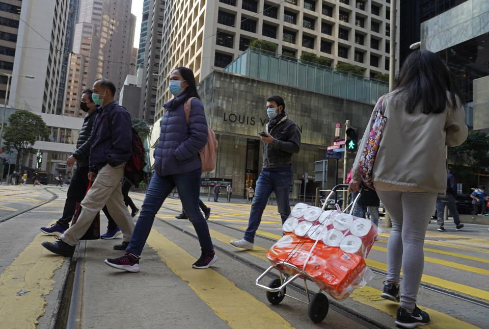 People wearing face mask walk at a downtown street in Hong Kong Monday, Feb. 17, 2020. COVID-19 viral illness has sickened tens of thousands of people in China since December. (AP Photo/Vincent Yu)