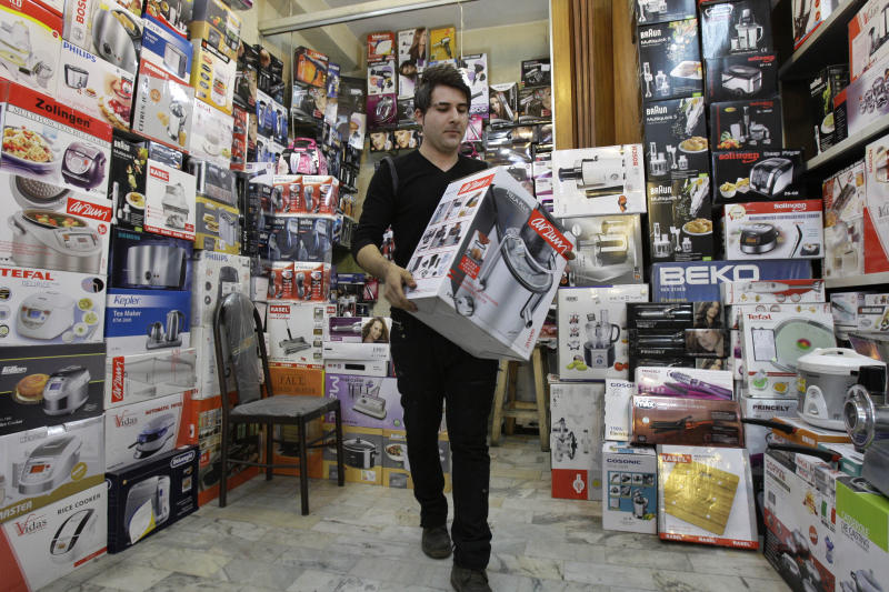 Iranian shopkeeper Masoud Hatami works at a home appliance store in Tehran, Iran, Thursday, Nov. 8, 2012. Sanctions-hit Iran has banned the import of foreign-made cars, laptops, and other 'luxury' goods in the hope of saving billions of dollars in hard currency, a state-owned newspaper reported Thursday. IRAN daily listed 75 products, from watches, home appliances and cell phones to coffee and toilet paper, that it said could no longer be purchased from abroad. But it says the ban does not apply to components used to produce the products. Iranian firms assemble many products including watches, laptops and cell phones. (AP Photo/Vahid Salemi)