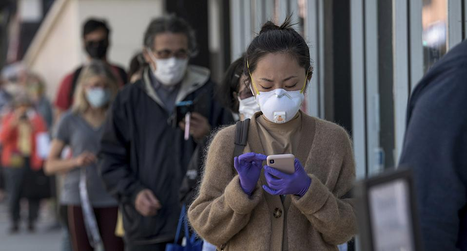 People wearing masks and using mobile phones