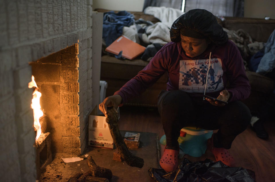 HOUSTON, TX - FEBRUARY 17: Linda McCoy throws wood on a fire for heat in her home in Houston, Texas on February 17, 2021. (Photo by Mark Felix for The Washington Post via Getty Images)