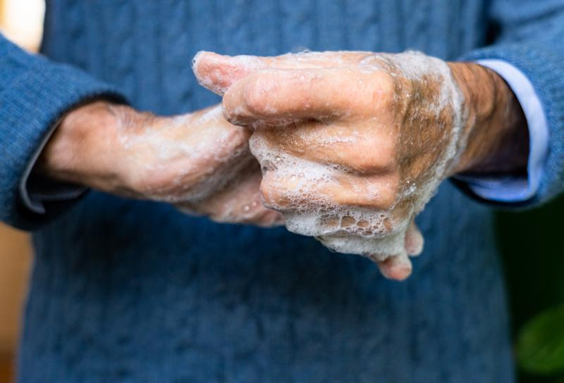 Close-up of an elderly man's hands as he carefully washes them with soap.