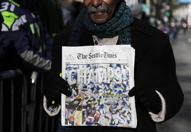 A fan stands with a signed newspaper along 4th Avenue in downtown at the Super Bowl victory parade for the Seattle Seahawks in Seattle, Washington February 5, 2014. Up to 500,000 Seattle Seahawks fans were expected to brave sub-freezing temperatures to celebrate the football team's first Super Bowl title at a parade set to wind through the city's downtown on Wednesday. REUTERS/Jason Redmond (UNITED STATES - Tags: SPORT FOOTBALL)