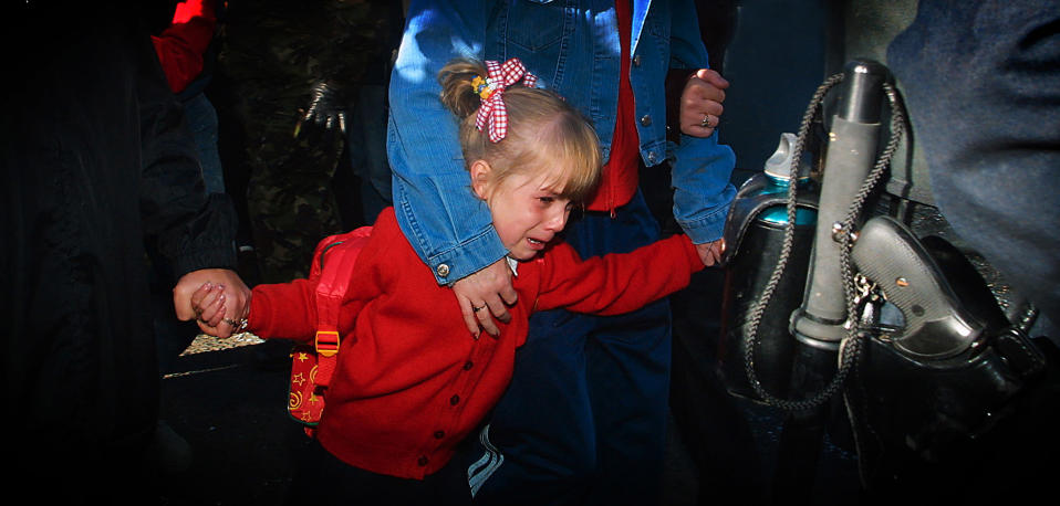 Alice-Lee Bunting clings to her mother as she walks to school in north Belfast in 2001 (Niall Carson/PA)