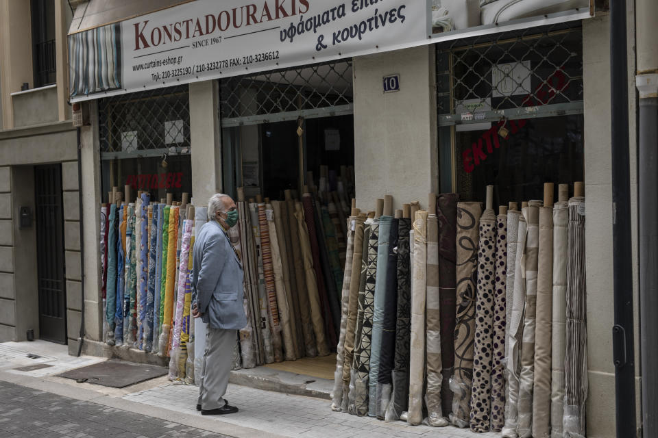 A man wearing a protective face mask waits outside a shop that sells fabrics central Athens, on Monday, April 5, 2021. Retail stores across most of Greece have been allowed to reopen despite an ongoing surge in COVID-19 infections, as the country battled to emerge from deep recession. (AP Photo/Petros Giannakouris)