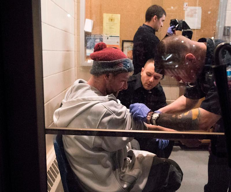 "Thirty one year-old Cody is checked out by paramedics as he enters the Safe Station program at the Central Fire Station March 28, 2018 in Manchester, New Hampshire. Safe Station transformed Manchester's 10 fire stations into intake centers where people struggling with addiction and want to enter treatment and begin their path to recovery can get help without fear of being arrested.Tucked away in the corner of a US fire station are two plastic chairs, a tiny poster saying ""anyone, anytime, can recover,"" and a poem in memory of a 20-year-old woman who fatally overdosed in 2016. The space is little more than a cubby hole, but has become a safe harbor for drug addicts in New Hampshire and symbol of hope in the US fight against the opioid crisis, a group of drugs, which like morphine, dulls pain and induces euphoria. / AFP PHOTO / Don EMMERT (Photo credit should read DON EMMERT/AFP/Getty Images)"