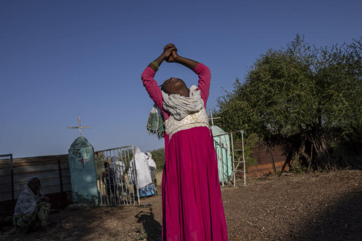 A Tigrayan woman who fled the conflict in Ethiopia's Tigray region stretches her arms after Sunday Mass ends at a nearby church, at Umm Rakouba refugee camp in Qadarif, eastern Sudan, Nov. 29, 2020. (AP Photo/Nariman El-Mofty)