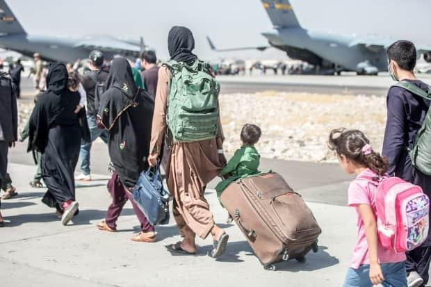 A woman pulls a suitcase with a child sitting on top during an evacuation at Hamid Karzai International Airport near Kabul, Afghanistan, on Tuesday. (Sgt. Samuel Ruiz/U.S. Marine Corps/Handout via REUTERS - image credit)
