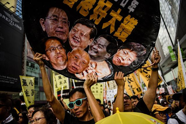 <p>A protester holds a wok-shaped artwork with pictures showing the faces of (top row L-R) Chairman of the Standing Committee of the National People's Congress of China Zhang Dejiang, Chinese President Xi Jinping, former chief executive of Hong Kong Leung Chun-ying, new Chief Executive of Hong Kong Carrie Lam, (bottom row L-R) Director of the Liaison Office of the Central People's Government in Hong Kong Zhang Xiaoming, former Hong Kong chief executive Tung Chee-hwa and Director of the Hong Kong and Macau Affairs Office Wang Guangya during a protest march in Hong Kong on July 1, 2017, coinciding with the 20th anniversary of the city's handover from British to Chinese rule. (Photo: Anthony Wallace/AFP/Getty Images) </p>