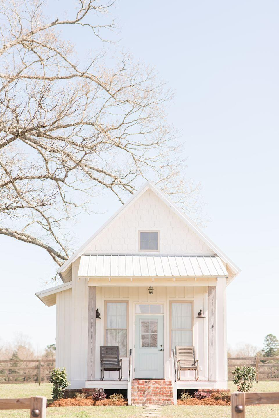 <p>We love the simplicity of a white farmhouse with a pale blue door. It's not too loud and works perfectly off of the sweet brick steps.</p>