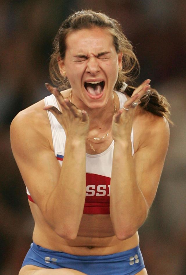 ATHENS - AUGUST 24: Yelena Isinbayeva of Russia celebrates after she completed a world record attempt in the women's pole vault final on August 24, 2004 during the Athens 2004 Summer Olympic Games at the Olympic Stadium in the Sports Complex in Athens, Greece. Isinbayeva of Russia broke the world record in the women's pole vault Tuesday with a vault of 16 feet, 1 1/4 inches (4.91 meters). (Photo by Mark Dadswell/Getty Images)