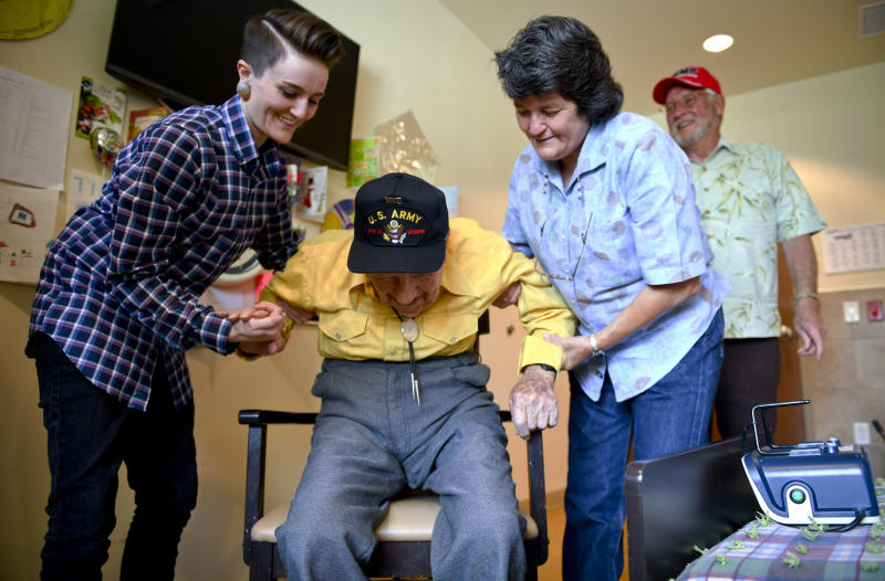 FILE - In this May 6, 2019, file photo, John R. Frey, center, a U.S. Army veteran, is helped out of a chair by his daughter, Janice Carlson, right, and granddaughter, Kara Carlson, as his son-in-law, Gary Carlson, stands by at the Mervyn Sharp Bennion Central Utah Veterans Home in Payson, Utah. Frey, a World War II veteran whose family hoped to help him get 101 cards for his 101st birthday say they have been overwhelmed and grateful as well over 5,000 cards have been sent to Frey.  (Isaac Hale/The Daily Herald via AP, File )