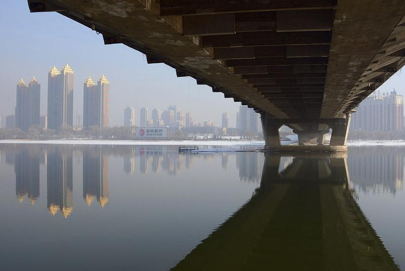 Newly-built residential buildings are seen next to the partially-frozen Songhua River and a bridge in Jilin