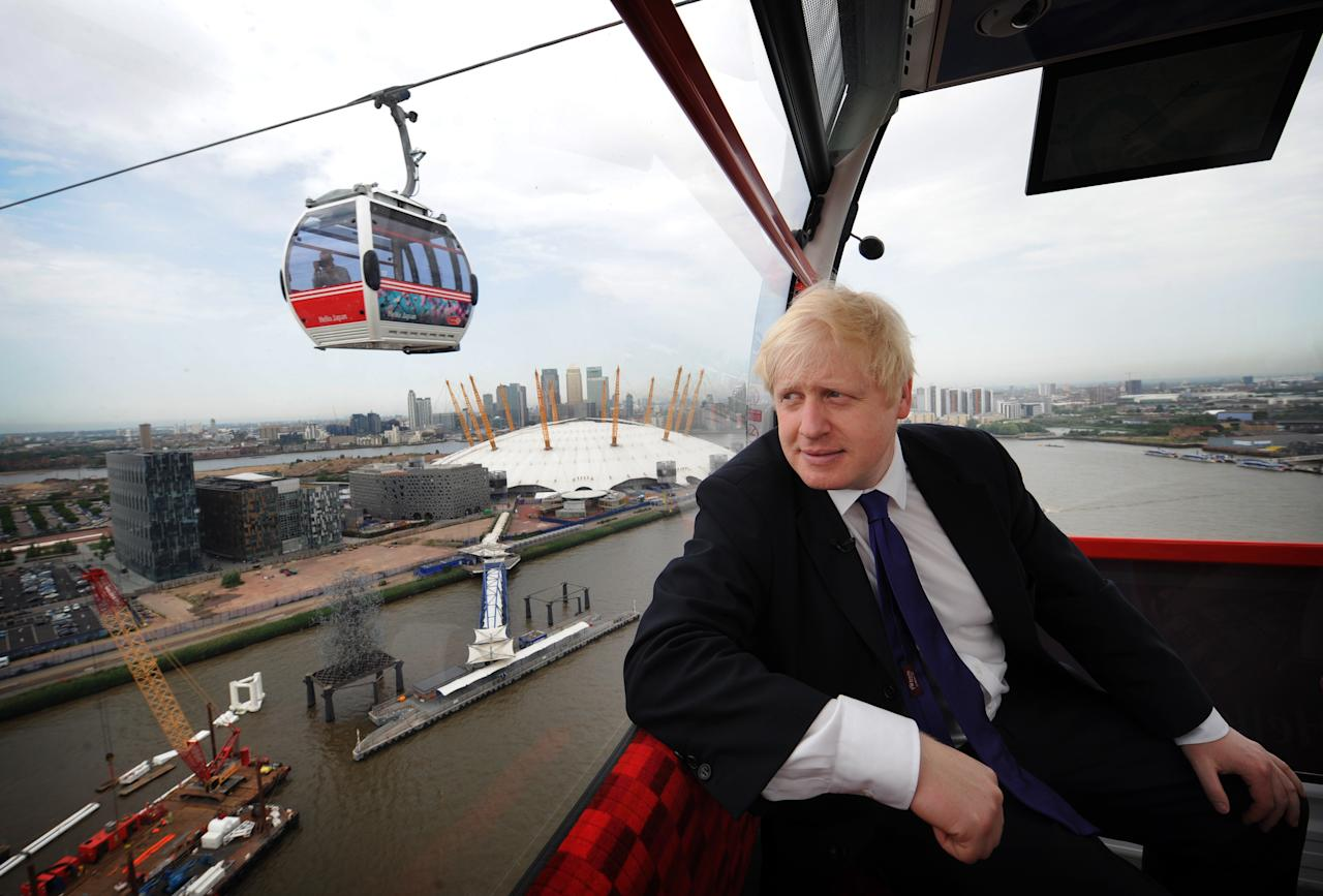 London Mayor Boris Johnson takes one of the first rides on the Emirates Air Line cable car across the River Thames prior to its official opening to the public this morning on June 28 in London, England. The Emirates Air Line, a £44 million cable car system spanning the Thames in London, was officially launched by London mayor Boris Johnson. Ahead of the public opening, Mr Johnson rode one of the cable cars which will whisk passengers almost 300ft above the river between Greenwich by the 02 Arena in south London and the Royal Docks by the ExCel exhibition centre to the north. Each car provides 360-degree views taking in the City, Canary Wharf, historic Greenwich, the Thames Barrier and the Olympic Park. (Photo by Stefan Rousseau WPA Pool/Getty Images)